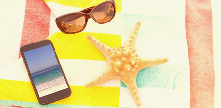 Close up of starfish with sunglasses and mobile phone kept on beach blanket against waters edge at the beach