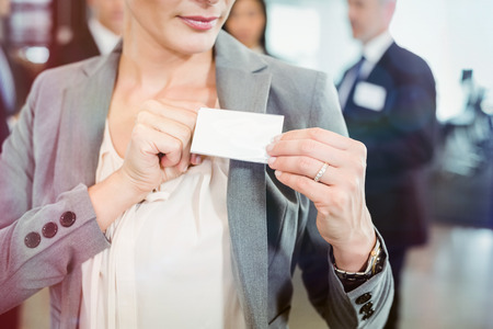 Close-up of businesswoman showing her badge in the office Stock Photo