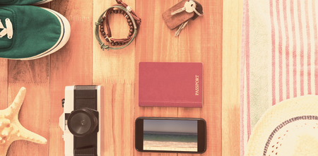 waters edge: Accessories and travel items on wooden board against waters edge at the beach