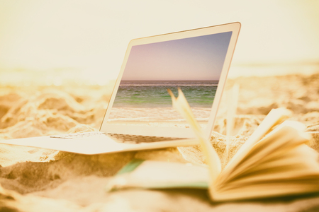 waters edge: Open book and laptop on sand against waters edge at the beach