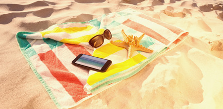waters edge: Starfish with sunglasses and mobile phone kept on beach blanket against waters edge at the beach