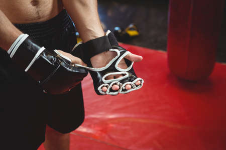 grappling: Boxer wearing grappling glove in fitness studio