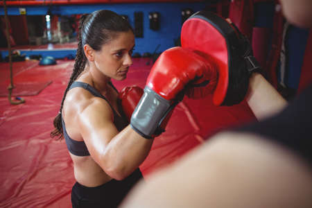 female boxer: Female boxer practicing with trainer at fitness studio LANG_EVOIMAGES
