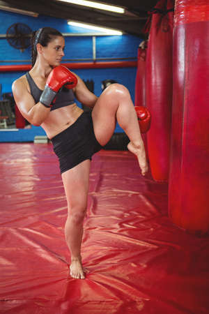 female boxer: Female boxer punching a boxing bag in fitness studio
