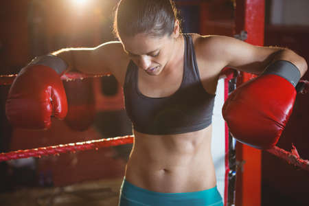 female boxer: Tired female boxer leaning on boxing ring in fitness studio LANG_EVOIMAGES