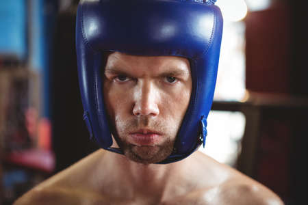 Portrait of boxer wearing boxing headgear in fitness studio LANG_EVOIMAGES