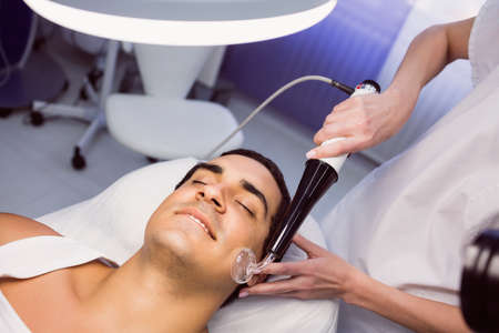 surgical removal: Dermatologist performing laser hair removal on patient face in clinic LANG_EVOIMAGES