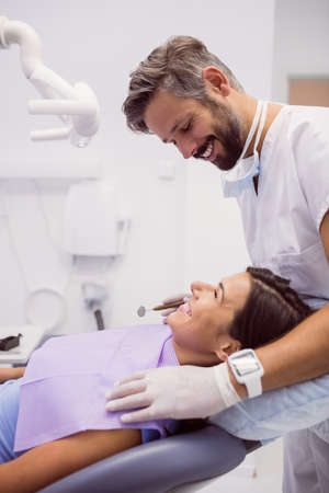 comunicacion oral: Dentist smiling while examining patient in clinic