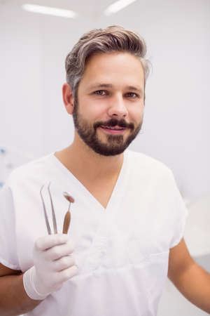 tweezers: Dentist holding dental tweezers and mouth mirror in clinic LANG_EVOIMAGES