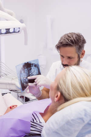 oral communication: Dentist showing x-ray to the patient in clinic