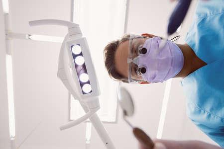 Close-up of dentist holding dental tools at dental clinic LANG_EVOIMAGES