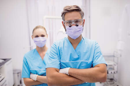 comunicacion oral: Portrait of dentist standing with arms crossed at dental clinic