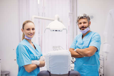 oral communication: Portrait of dentist standing with arms crossed at dental clinic