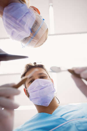 oral communication: Close-up of dentists holding dental tools at dental clinic