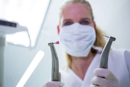 comunicacion oral: Female dentist with surgical mask holding dental instruments at clinic LANG_EVOIMAGES