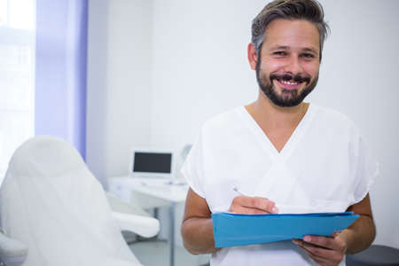 orthodontist: Portrait of smiling doctor writing on medical reports in clinic LANG_EVOIMAGES