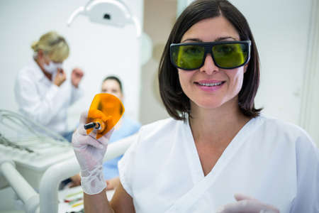 Dentist holding a dental curing ultraviolet light at clinic LANG_EVOIMAGES