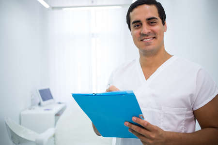 comunicacion oral: Portrait of smiling doctor holding a medical file