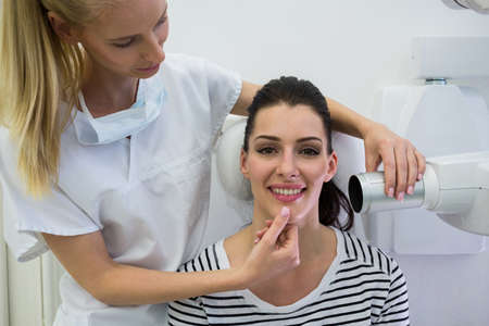 oral communication: Dentist taking a female patients tooth x-ray in clinic