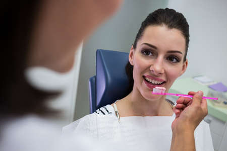 comunicacion oral: Dentist holding a brush in front of patient at clinic