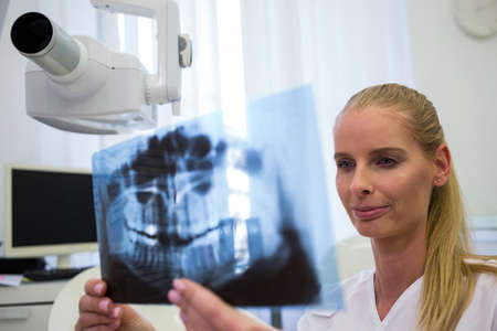 comunicacion oral: Dentist looking at dental x-ray plate in clinic