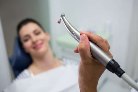 comunicacion oral: Close-up of dentist holding a dentistry, dental handpiece while examining a woman at clinic LANG_EVOIMAGES