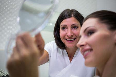 comunicacion oral: Paciente que controla sus dientes en el espejo en la clínica dental