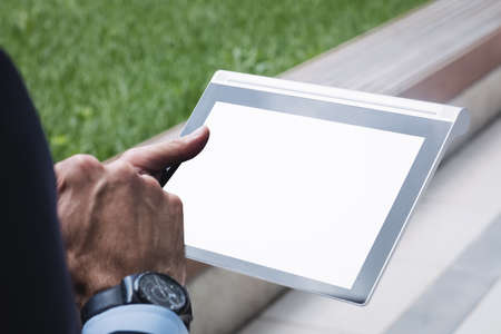 Close-up of a businessman using digital tablet outside office building