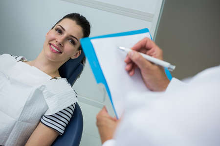 comunicacion oral: Doctor writing on clipboard while patient lying on dental bed in dental clinic LANG_EVOIMAGES