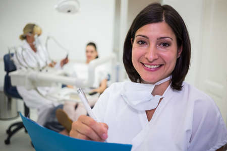 comunicacion oral: Portrait of female dentist writing report in dental clinic LANG_EVOIMAGES