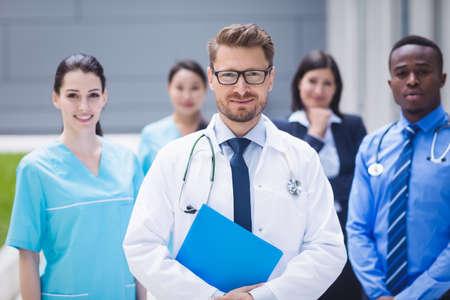 premises: Portrait of smiling doctors standing together in hospital premises LANG_EVOIMAGES