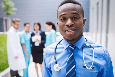 premises: Portrait of smiling doctor standing in hospital premises