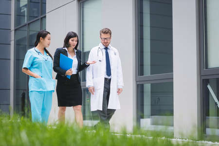 premises: Doctors and nurse interacting while walking in hospital premises LANG_EVOIMAGES
