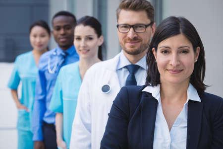 premises: Portrait of smiling doctors standing in row at hospital premises
