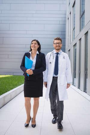 premises: Smiling doctors walking together in hospital premises