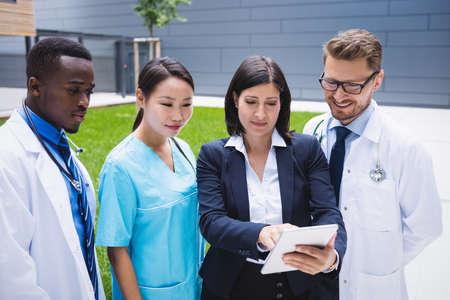 premises: Team of doctors discussing over digital tablet in hospital premises LANG_EVOIMAGES