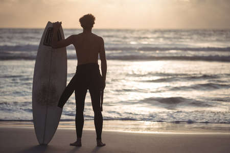 Rear view of a man carrying surfboard standing on beach at dusk