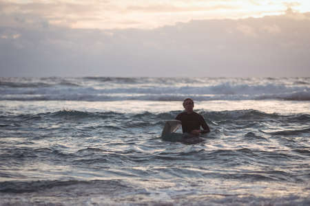Portrait of a man carrying surfboard coming out of sea at dusk LANG_EVOIMAGES