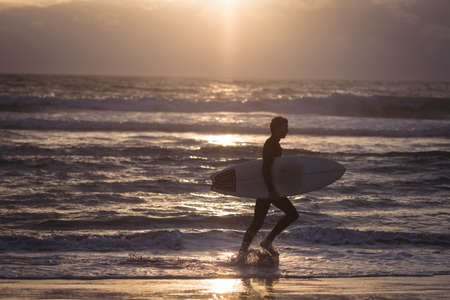 Silhouette of a man carrying surfboard walking on beach at dusk