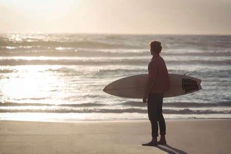 Man carrying surfboard standing on beach at dusk