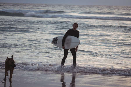 Man carrying surfboard standing on beach with his dog at dusk