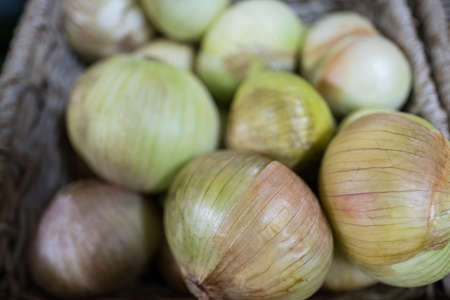 Close-up of fresh onions in wicker basket