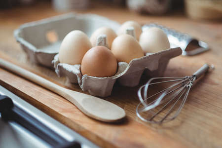 whisker: Eggs, whisker and wooden spoon on table in kitchen