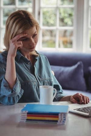 tensed: Tensed woman using laptop in living room at home