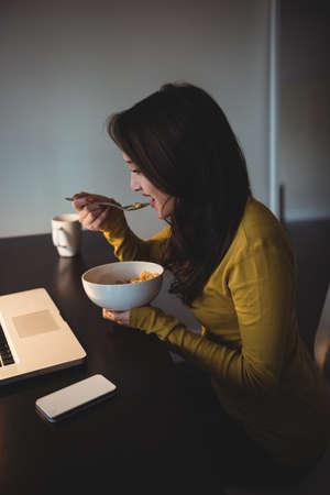 comiendo cereal: Mujer que come el cereal mientras se trabaja en la computadora portátil en la sala de estudio en el hogar