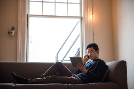 mobilephone: Man talking on mobilephone in living room at home