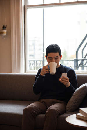 mobilephone: Man using mobilephone while having a cup of coffee at home LANG_EVOIMAGES