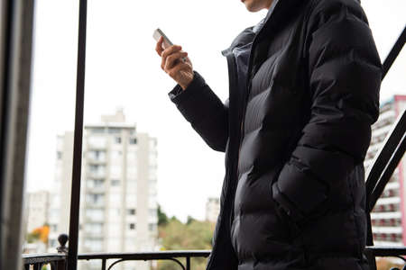 mobilephone: Mid-section of man using mobilephone in balcony LANG_EVOIMAGES