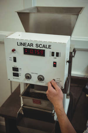 weighing machine: Hand of man using a coffee weighing machine