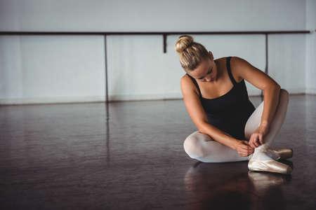 Ballerina adjusting stockings while sitting in ballet studio